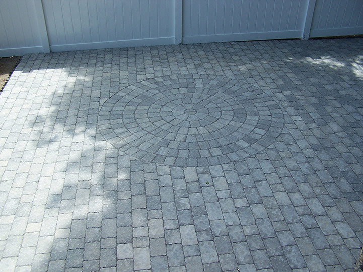 White and grey patio pavers with inlaid circle.