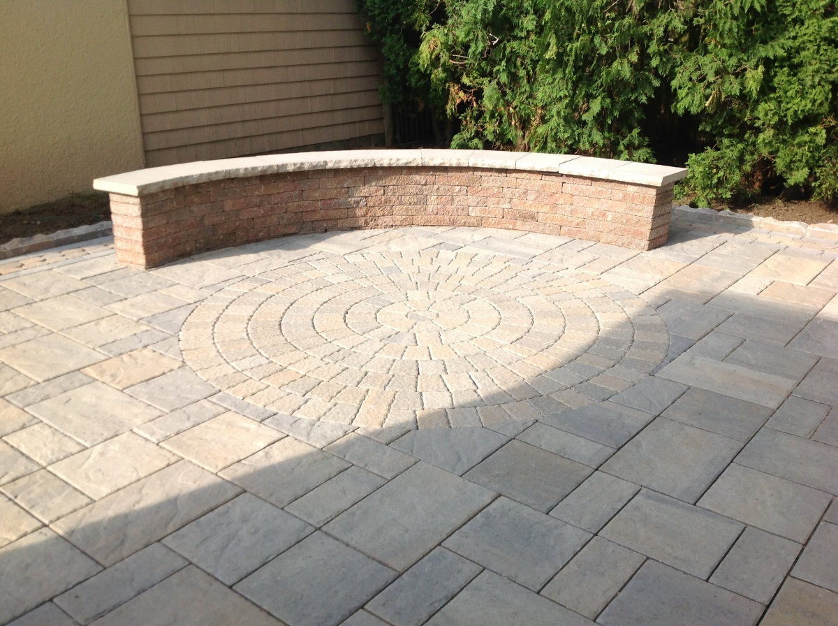patio with inlaid circle and curved sitting wall with cap