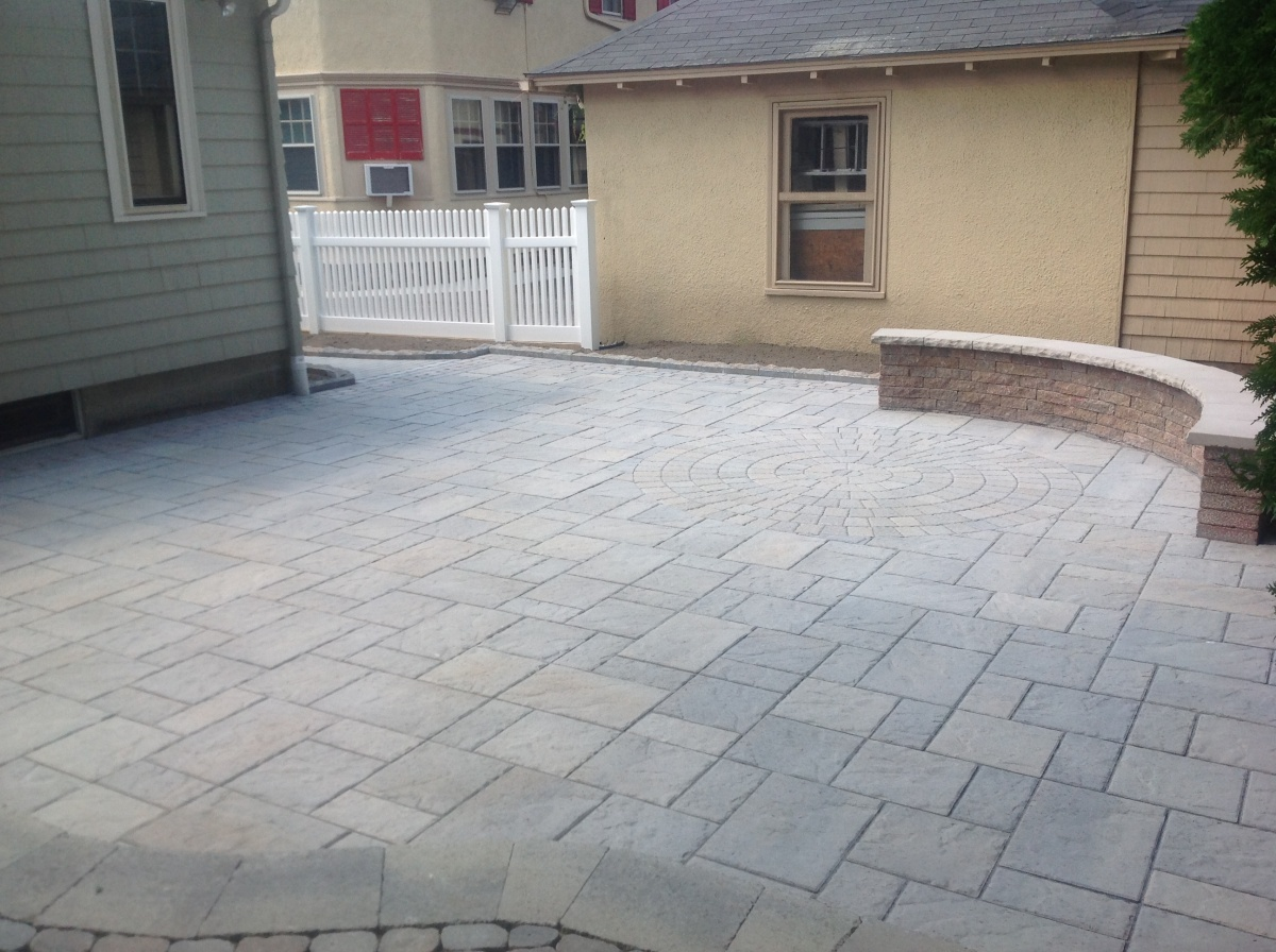 Patio with inlaid circle and curved sitting wall with cap.