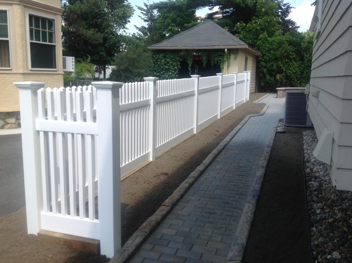 Open vinyl fencing frames paver walkway.