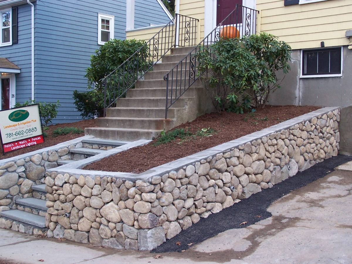 Natural fieldstone retaining walls with cement cap and fieldstone steps
