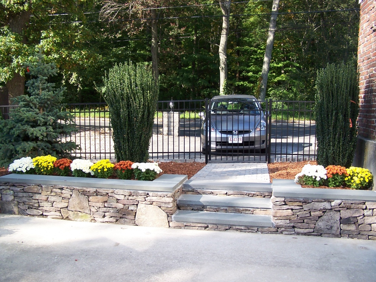 Natural fieldstone wall and metal fence