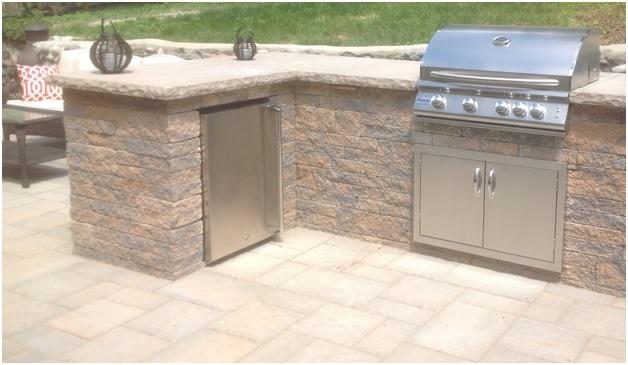 Outdoor kitchen island: Grill with cabinet storage & refrigerator.